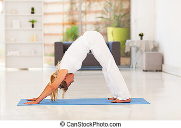 senior woman doing yoga at home