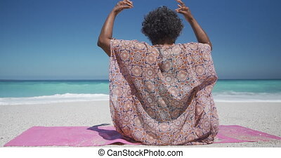 Senior woman doing yoga at the beach
