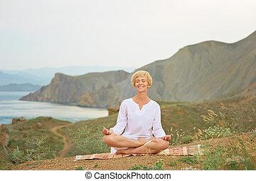 Senior woman doing yoga exercises with mountain on the...