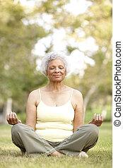 Senior Woman Doing Yoga In Park