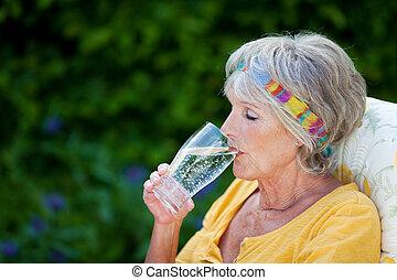 senior woman, drickande, mousserande vatten, i park