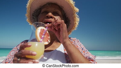 Senior woman drinking a cocktail at the beach - Low angle ...