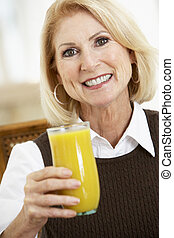 Senior Woman Drinking A Glass Of Fresh Orange Juice