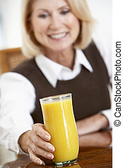 Senior Woman Drinking A Glass Of Fresh Orange Juice