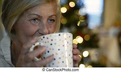 Senior woman drinking at Christmas time. - Senior woman in...