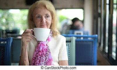 Senior Woman Drinking Coffee And Looking Out Of Window
