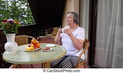 Senior woman drinking her coffee on terrace in summertime