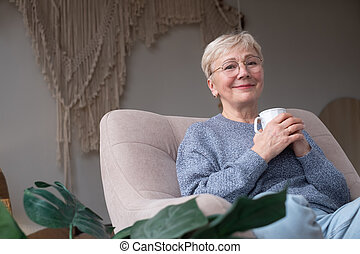 Senior woman drinking hot drink sitting at home on sofa
