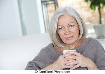 Senior woman drinking hot drink
