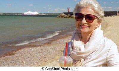 senior woman drinking shake on summer beach - people and...