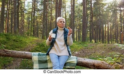 senior woman drinking tea and eating pie in forest - picking...