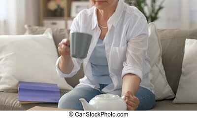 senior woman drinking tea at home - age, drink and people...