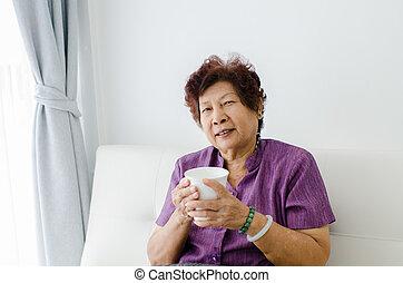 senior woman drinking tea at home.