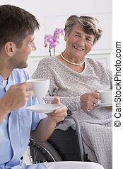 Senior woman drinking tea with her caregiver - Senior woman...