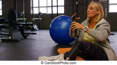Senior woman drinking water in fitness studio 4k - Senior...