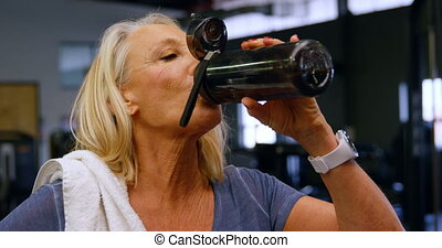 Senior woman drinking water in fitness studio 4k