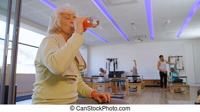 Tired senior woman drinking water in yoga center 4k
