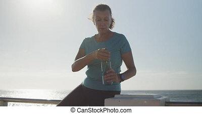 Senior woman drinking water on a promenade - Senior ...