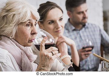 Senior woman drinking wine - Senior woman drinking red wine...