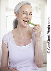 Senior Woman Eating A Celery Stick