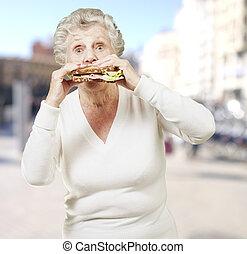 senior woman eating a healthy sandwich against a street background
