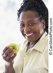 Senior Woman Eating Green Apple And Smiling At The Camera