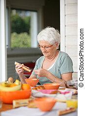 Senior woman eating on her terrace
