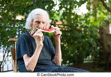 Senior woman eating watermelon outdoors - Senior woman...