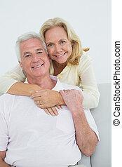 Senior woman embracing man from behind at home