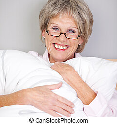 Senior Woman Embracing Pillow