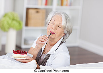 Senior woman enjoying a fruity cream cake