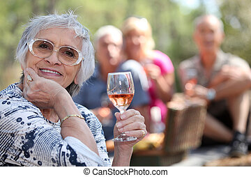 Senior woman enjoying a glass of rose wine with friends on a picnic