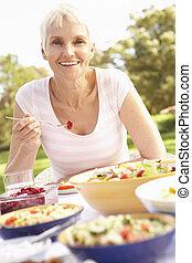 Senior Woman Enjoying Meal In Garden