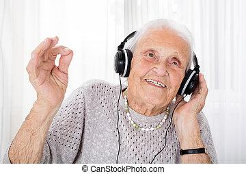 Senior Woman Enjoying Music With Headphone - Portrait Of...