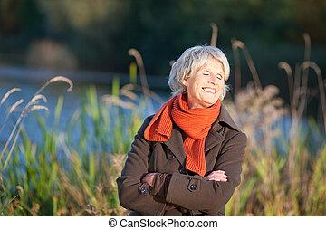 Senior Woman Enjoying Sunlight In Park