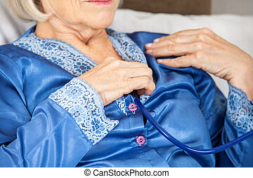 Senior Woman Examining Herself With Stethoscope
