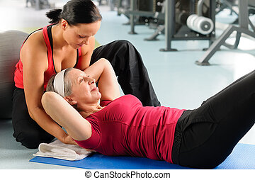 Senior woman exercise abdominal in fitness center - Fitness...