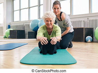 Senior woman exercising at gym with coach