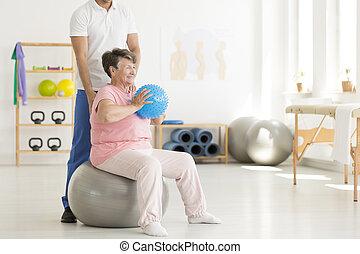 Senior woman exercising in clinic