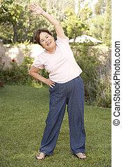 Senior Woman Exercising In Garden