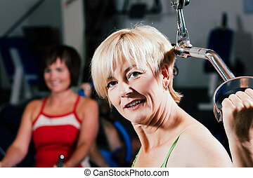 Senior woman exercising in gym - Senior woman in the gym...