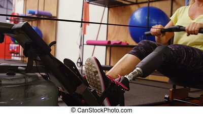 Senior woman exercising on water rower machine in fitness studio 4k