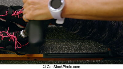 Senior woman exercising on water rowing machine in fitness...