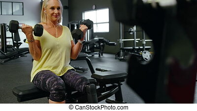 Senior woman exercising with dumbbell in fitness studio 4k -...