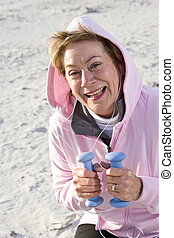Senior woman exercising with hand weights on beach