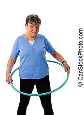 Senior woman exercising with hula-hoop