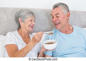 Senior woman feeding cereals to husband