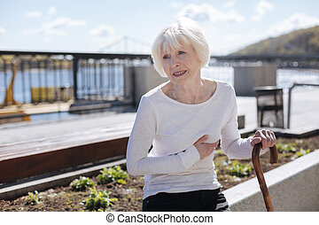 Senior woman feeling pain in chest on the quay