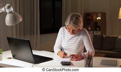 senior woman filling tax form at home in evening -...
