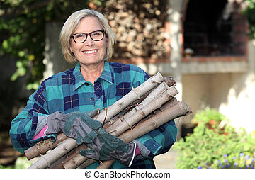 senior woman gathering wood in the garden